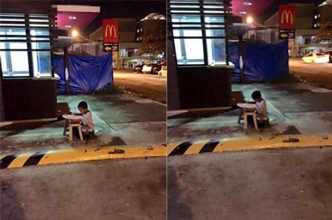 A foto que emocionou o mundo: menino, morador de rua, usa luz do McDonald's para fazer lição de casa.