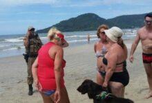 Foto de Mulher tenta expulsar deficiente visual de praia por causa de cão-guia